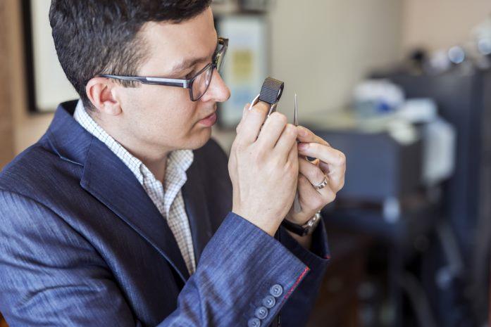 Jeweler examining cuts on a large diamond