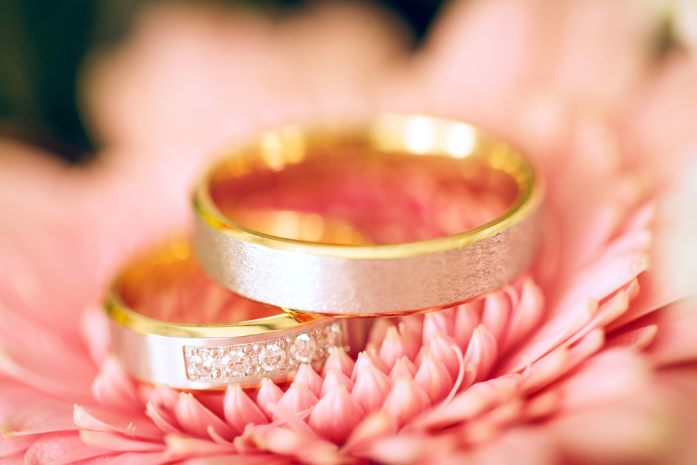 Beautiful shiny wedding rings with diamonds closeup on a flower background