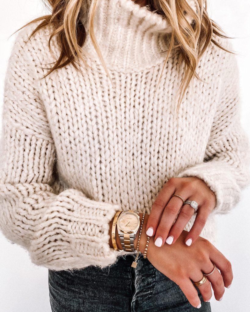 A woman wearing diamonds and a bulky sweater