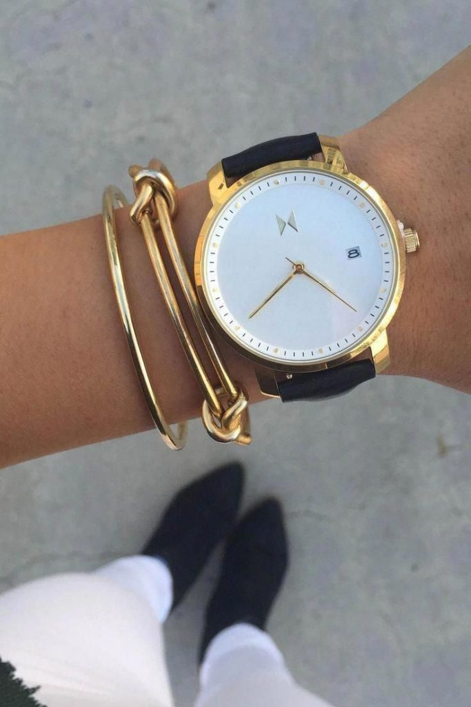 A watch highlighted by a couple of simple gold bangles