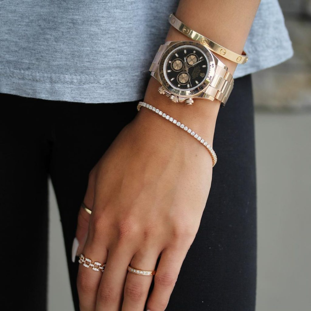 A woman wearing a thin, diamond bracelet with a few rings and a men's watch