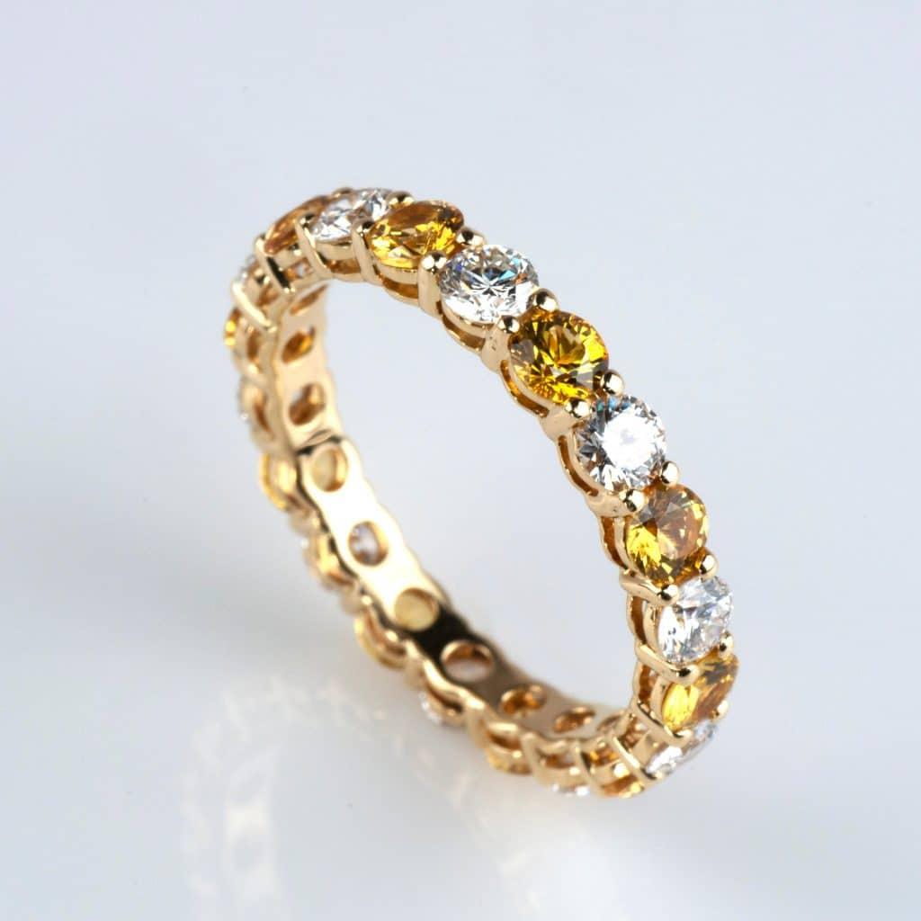 Alternating yellow and white diamond infinity yellow gold ring